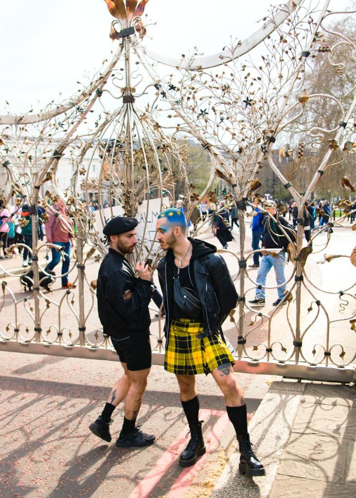 Zwei Demonstranten stehen vor einem Tor und tragen Schottenrock un gefärbte Haare in Europafarben