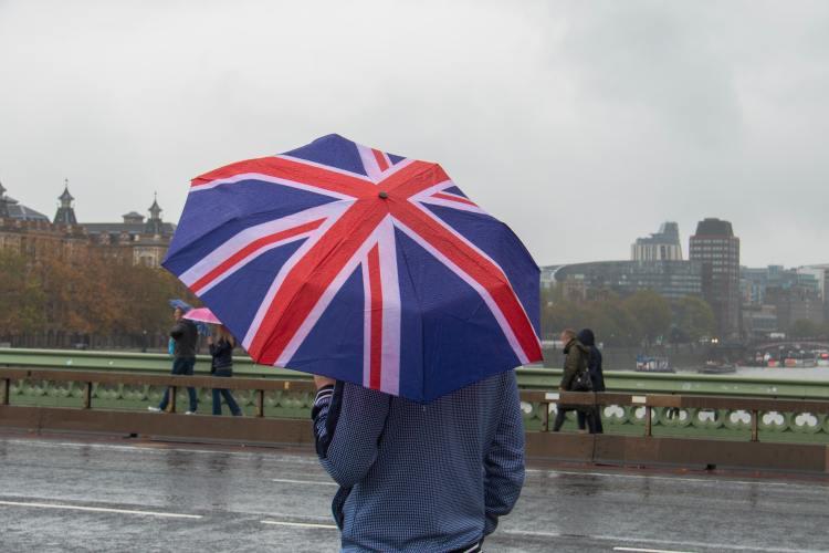 Person hält Regenschirm mit Aufdruck der Großbritannien-Flagge