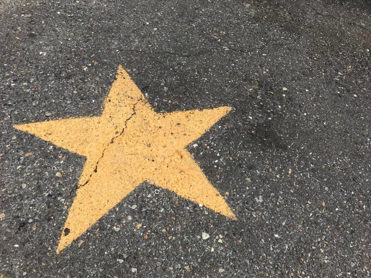 Gelber Stern ist auf Asphalt gemalt
