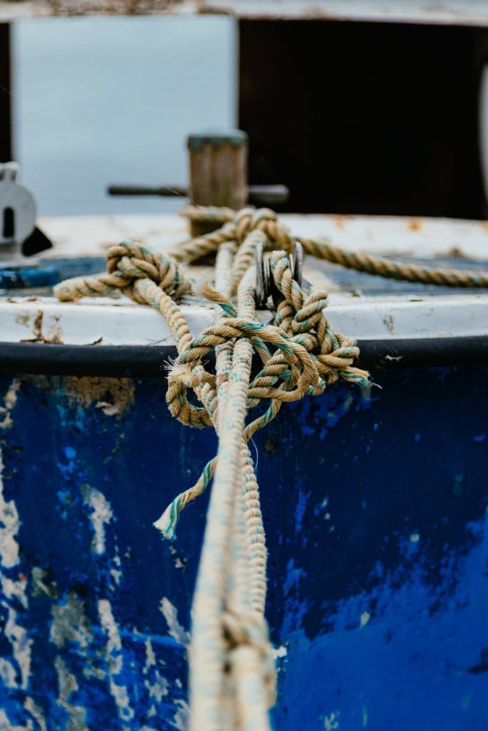 Nahaufnahme eines dicken Seils, welches ein Boot sichert.