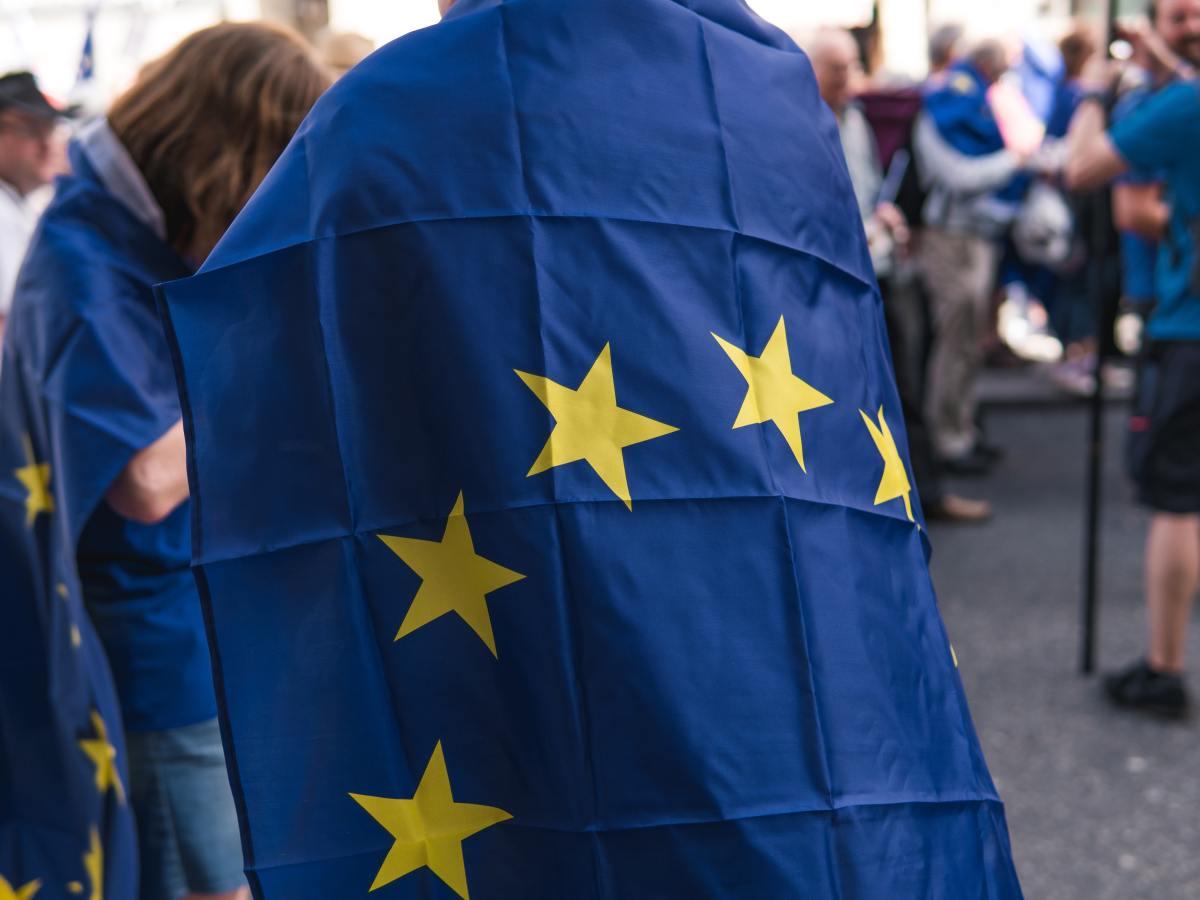 Person trägt Flagge der Europäischen Union als Umhang