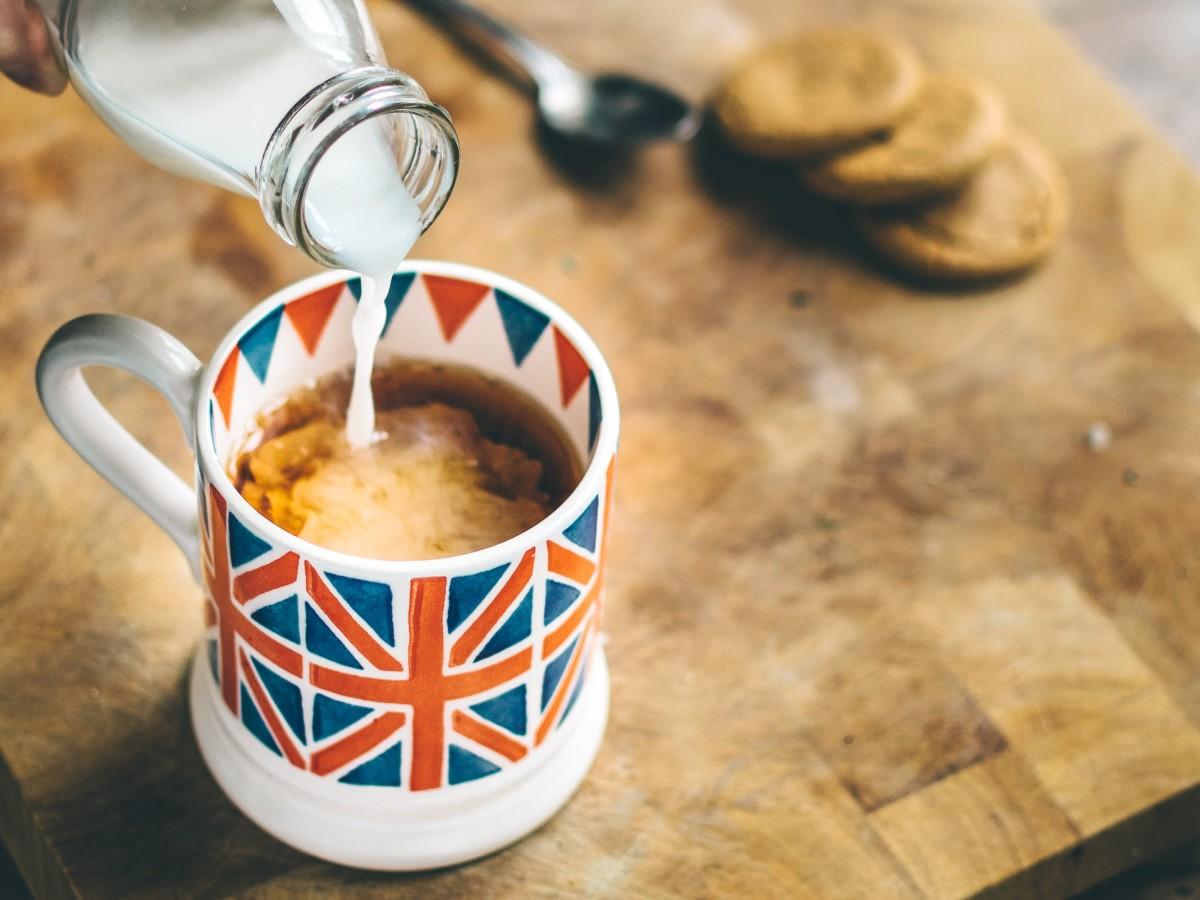 Milch wird in Teetasse gegossen