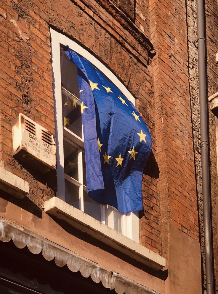Backsteingebaäude mit wehender Europaflagge am Fenster.